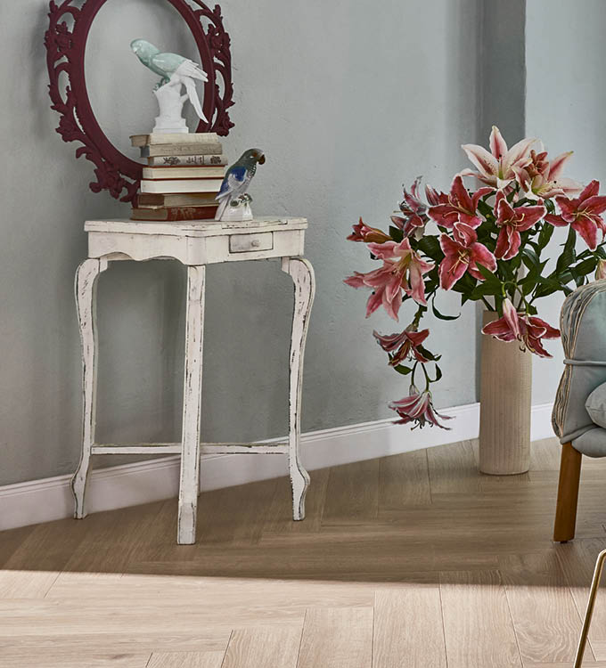 Heller Laminat-Boden in Dekoecke mit Tischchen und Blume | Stuke Holz