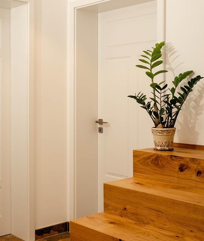 Weiße Tür und Holztreppe von Stuke Holz.