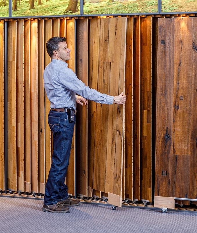 Berater zeigt die Bodenauswahl in der Ausstellung von Stuke Holz.