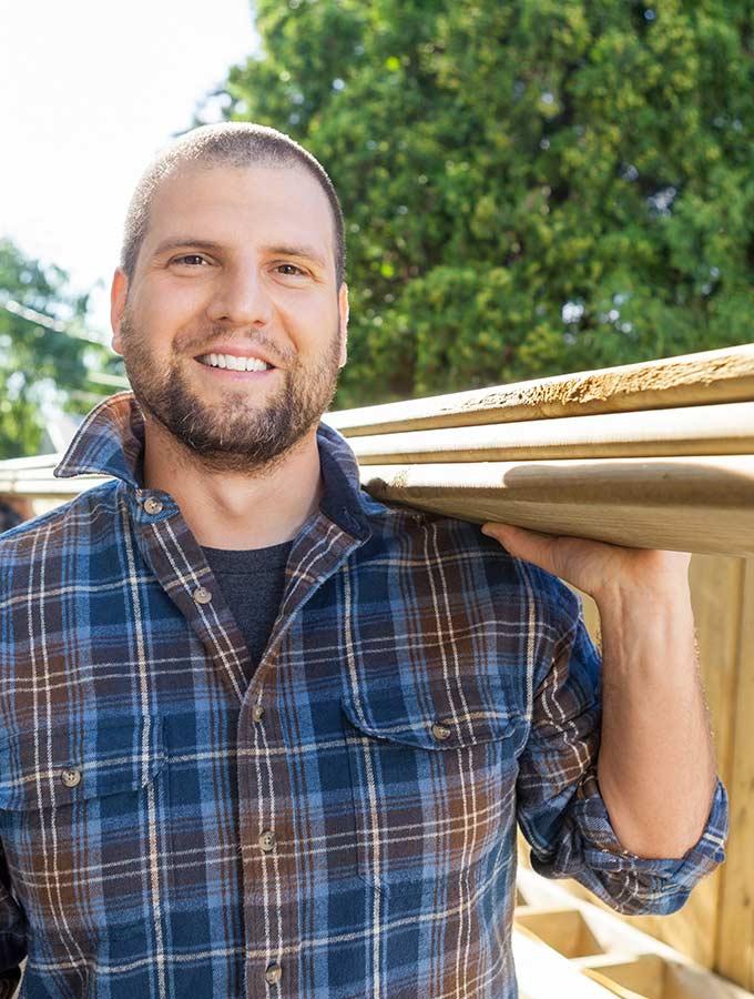 Monteur trägt Holzbretter und lacht | Personalsuche | Stuke Holz